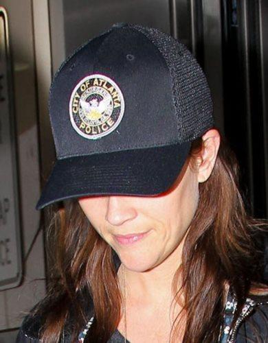 警察のキャップをかぶって空港に降り立った女優リース・ウィザースプーン
