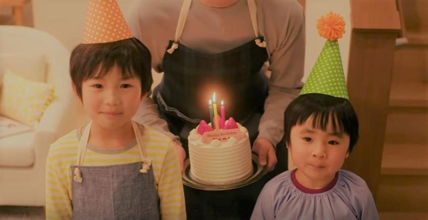 暗闇の中からパパがロウソクに火を灯したケーキを手に現れる