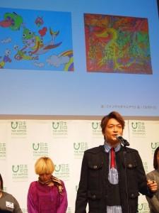 後方画面に映し出された自身の作品について説明する香取慎吾