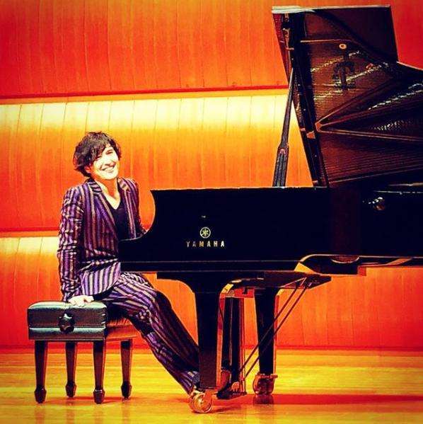 ピアノを前に微笑む清塚信也(画像は『清塚信也 2018年3月21日付Instagram「福岡ありがとうございました。」』のスクリーンショット)