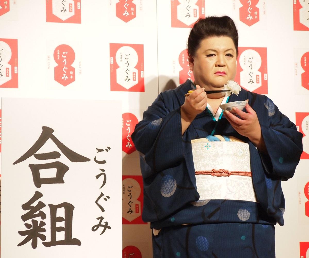 新ブレンド米の名称の隣で試食するマツコ・デラックス