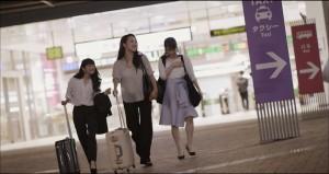 女性3人がスーツケースを手に旅行へ
