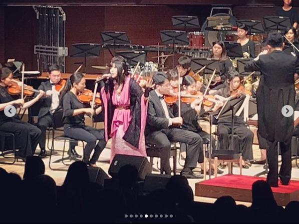 鈴華ゆう子、オーケストラをバックに熱唱(画像は『鈴華ゆう子 2019年5月20日付Instagram「東京音楽大学中目黒・代官山校こけら落とし鈴華ゆう子スペシャルコンサートでした。」』のスクリーンショット)
