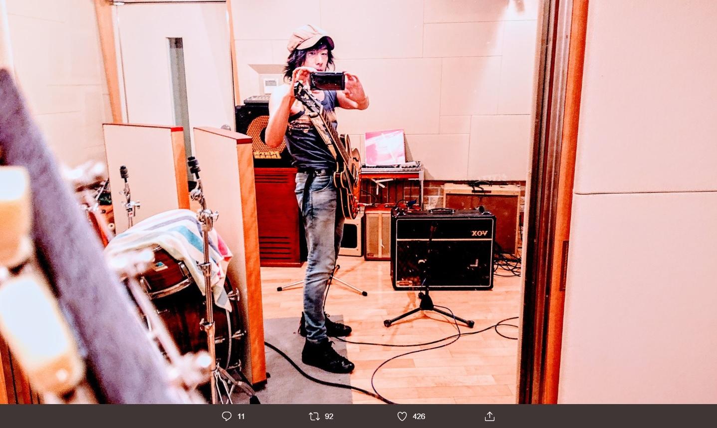 ギターを肩から下げたNAOKI(画像は『NAOKI PSYCHEDELICO 2019年10月19日付Twitter「無宗教ですが、MIX作業を中断してこの期に及んで思いついてしまったギターのダビングレコーディングに戻ってしまっている僕を、神様お許しください」』のスクリーンショット)