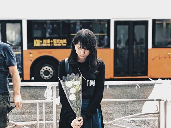 花を手向ける周庭さん(画像は『周庭 Agnes Chow 2019年6月17日付Instagram「200萬人上街了,你看到嗎。」』のスクリーンショット)