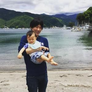 甥を抱く古市憲寿氏(画像は『古市憲寿 2016年6月3日付Instagram「昔、家族で行った場所に。すぐに泣かれるの巻。」』のスクリーンショット)
