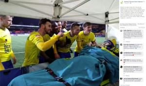 サッカー場で選手たちに囲まれる男性(画像は『Stichting Ambulance Wens Nederland 2020年2月21日付Facebook「Gisteren kon deze meneer toch nog naar een wedstrijd van zijn club SC Cambuur.」』のスクリーンショット)