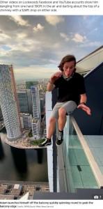 命綱なしで手すりの上に座るアダムさん(画像は『The Sun 2020年6月19日付「HIGH AND FRIGHTY Heart-stopping moment teenage daredevil pretends to throw himself off 600ft high balcony」(Credit: SWNS:South West News Service)』のスクリーンショット)