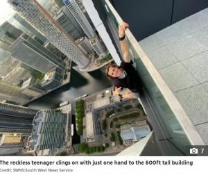 片手で手すりにぶら下がるアダムさん(画像は『The Sun 2020年6月19日付「HIGH AND FRIGHTY Heart-stopping moment teenage daredevil pretends to throw himself off 600ft high balcony」(Credit: SWNS:South West News Service)』のスクリーンショット)