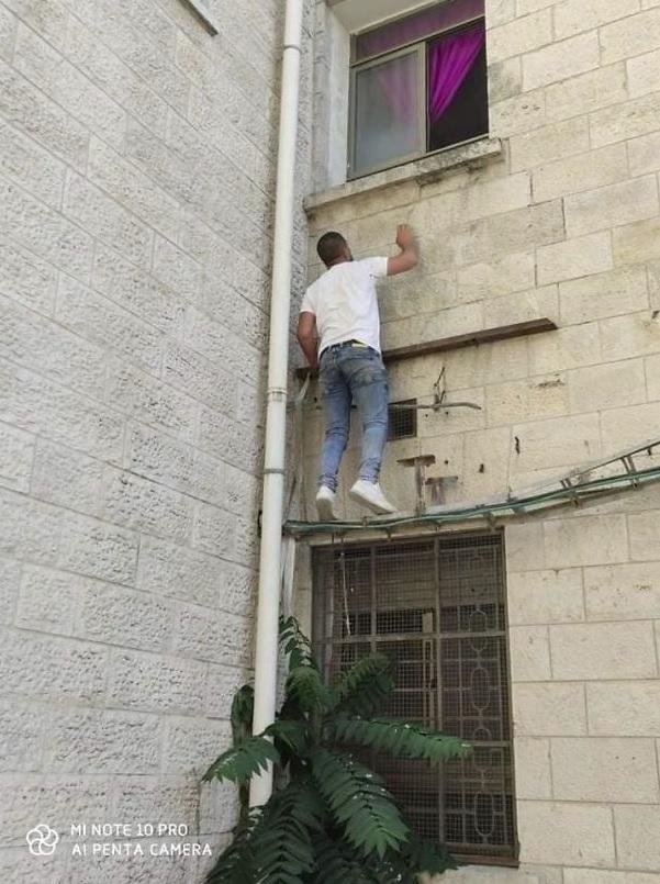 病院の壁をよじ登るジハードさん(画像は『Bored Panda 2020年7月21日付「Man Climbs Up Hospital Wall And Watches Over His Mom From Outside The Hospital Day And Night Until She Dies Due To Coronavirus」』のスクリーンショット)