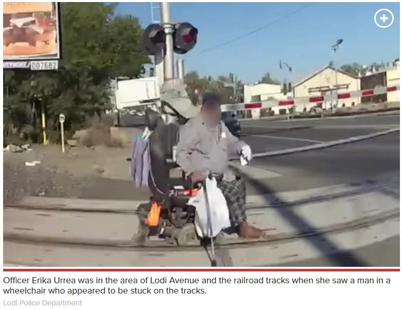 車いすの車輪がレールに挟まってしまった男性(画像は『New York Post 2020年8月13日付「California cop saves man whose wheelchair got trapped in train tracks」(Lodi Police Department)』のスクリーンショット)