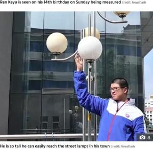 街灯にも手が届いてしまう(画像は『The Sun 2020年10月20日付「NEW HEIGHTS This is the 14-year-old Chinese boy who measures well over 7 feet tall and is set to become the tallest male teenager」(Credit: Newsflash)』のスクリーンショット)