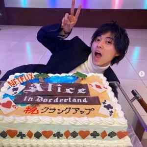 『今際の国のアリス』クランクアップ記念ケーキの横でおどける山崎賢人(画像は『桜田 通 Dori Sakurada 2020年12月12日付Instagram「賢人がインスタでバースデーイベントにサプライズゲストで来てくれた時の写真を載せてくれたので、お返しに『今際の国のアリス』の打ち上げの時のクランクアップ記念ケーキとの写真を載せます」』のスクリーンショット)