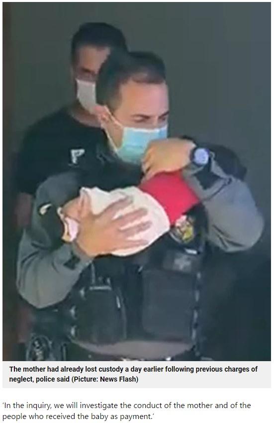 警察官に保護される男児(画像は『Metro 2021年6月12日付「Mum 'uses two-month-old baby as guarantee on her drug debts'」(Picture: News Flash)』のスクリーンショット)